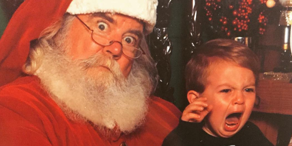 A freaked out Santa Claus and crying kid pose together to form an exceptionally awkward picture.