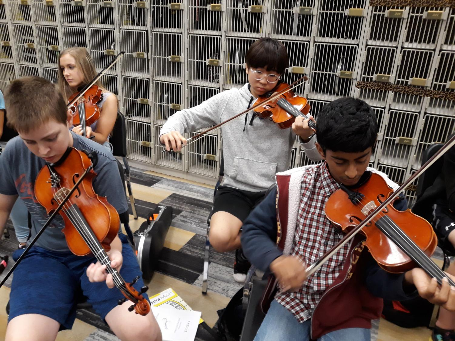 Violin and viola students play their instruments in 4th period orchestra class.