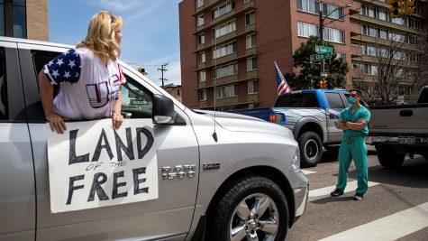 A man in scrubs blocks a protestor in Colorado.