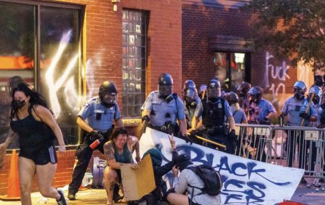 Police mace protestors sitting down holding a Black Lives Matter sign.